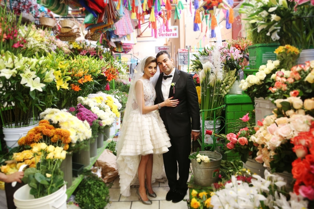 A couple posing at a market surrounded by fresh flowers